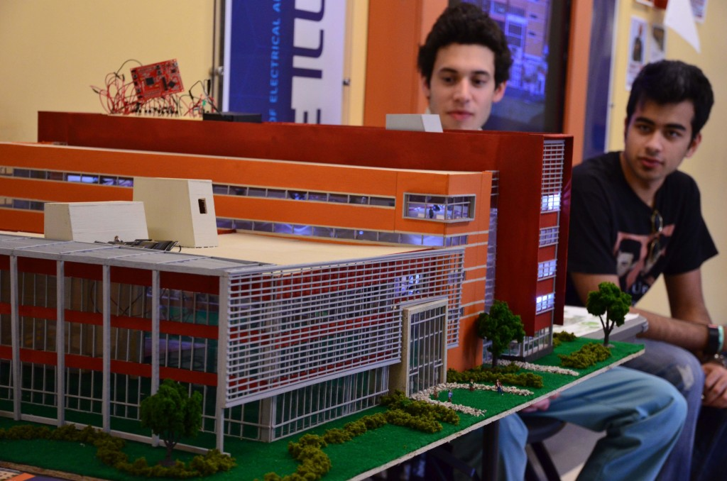Guillermo Acevedo (left) and Kavish Munjal (right) help Thomas Navidi present the model at EOH.